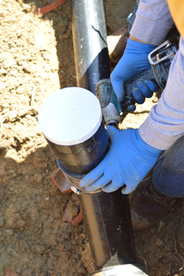 an Oakland sewer repair specialist is checking a newly installed sewer pipe
